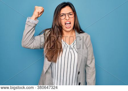 Young hispanic business woman wearing glasses standing over blue isolated background angry and mad raising fist frustrated and furious while shouting with anger. Rage and aggressive concept.
