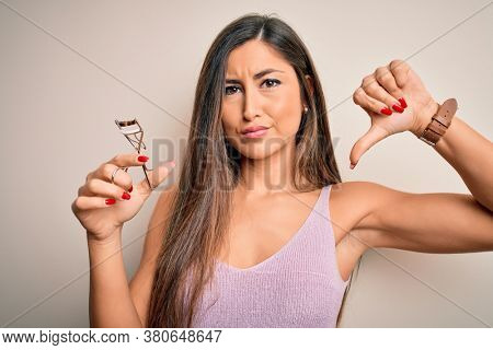 Young beautiful brunette woman holding eyelash curler over isolated white background with angry face, negative sign showing dislike with thumbs down, rejection concept