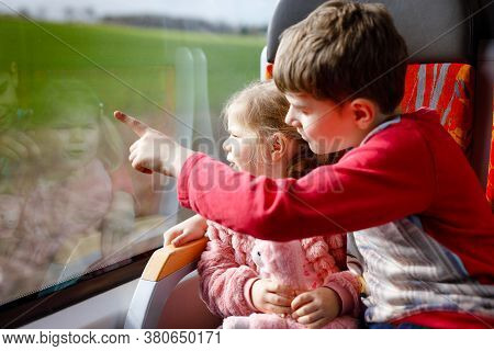 Cute Little Toddler Girl And Brother Kid Boy Sitting In Train And Looking Out Of Window. Two Adorabl
