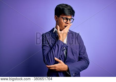 Young handsome business man wearing jacket and glasses over isolated purple background bored yawning tired covering mouth with hand. Restless and sleepiness.