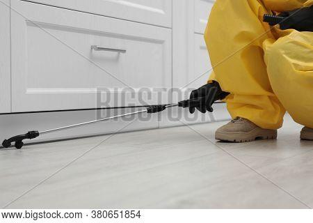 Pest Control Worker Spraying Pesticide Around Furniture Indoors, Closeup