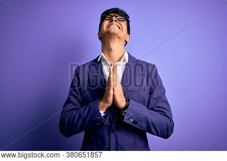 Young handsome business man wearing jacket and glasses over isolated purple background begging and praying with hands together with hope expression on face very emotional and worried. Begging.