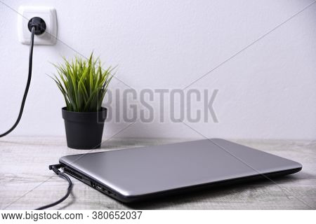 Laptop, Computer Is Charging From A 220-volt Outlet On A Desk Near The Wall. Energy, Accumulation. M