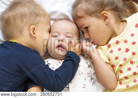 Little Smiling Kids Playing Together Sitting On Bed. Brother And Sister Kiss A Newborn.toddler Kid M