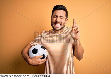 Handsome player man with beard playing soccer holding footballl ball over yellow background gesturing finger crossed smiling with hope and eyes closed. Luck and superstitious concept.