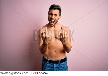 Young handsome strong man with beard shirtless standing over isolated pink background Showing middle finger doing fuck you bad expression, provocation and rude attitude. Screaming excited