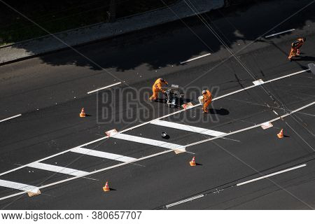 Ukraine, Kyiv - May 25, 2020: Road Workers Painting Marking White Line On The Road Surface. Thermopl