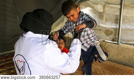 Aleppo, Syria, January 15, 2020:\na Physiotherapist Does Rehabilitation Therapy To A Child Lying On