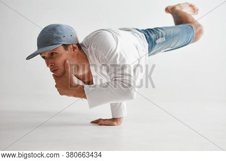 Cool Guy Breakdancer Stands On One Hand Dancing Lower Break Dance And Thinking, Isolated On White Ba