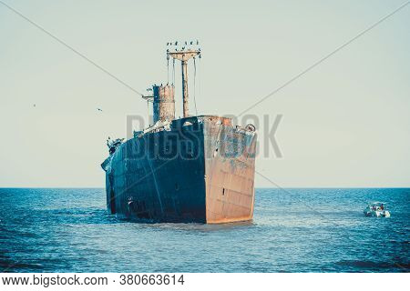 A Shipwreck On A Sandbank In The Sea. Rusty Wreck Abandoned At Sea.