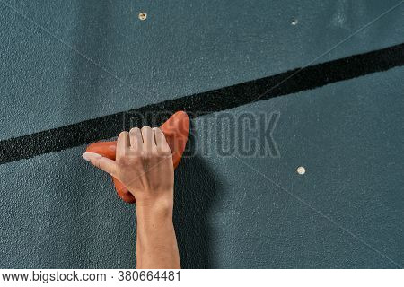 Close Up Of A Hand Of Woman Climbing Up On Rock Wall In Gym. Bouldering Training Concept. Focus On H