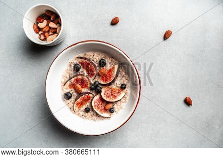 Oatmeal With Berries, Nuts And Honey. Breakfast: Oatmeal, Blueberry And Figs On A Light Background,