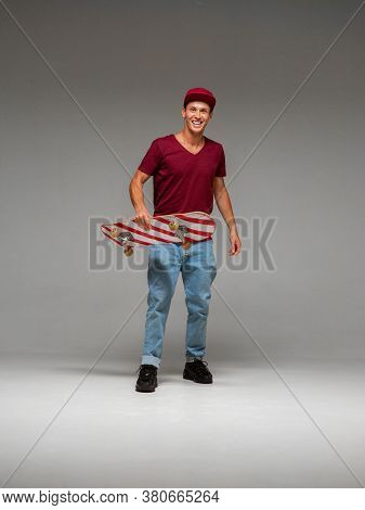Cool Laughing Guy Skateboarder In Cap Stands With Skateboard In Studio On Grey Background. Photo Abo