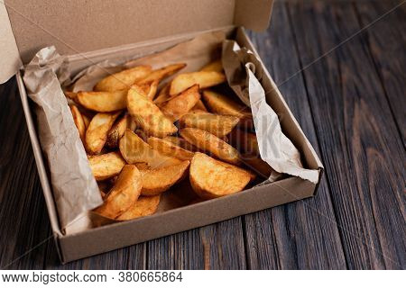 Slices Of Fried Potatoes In Box For Food Delivery. Delivered Take Away Fast Food On Wooden Backgroun
