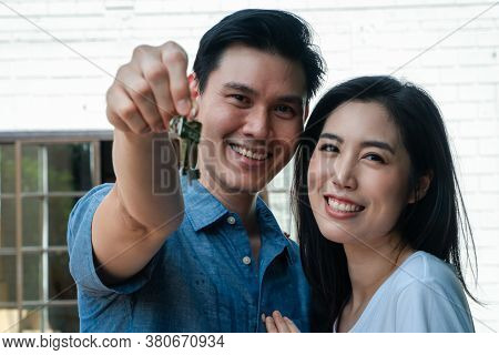 Happy Smiling Couple In Front Of The Home And Holding Keys To New Home On Moving In Day, And Start A