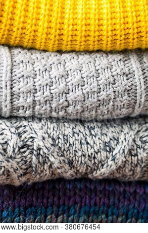Fall Background From Close Up Stack Or Pile Of Fashionable Knitted Colors Wool Clothes Or Sweaters W