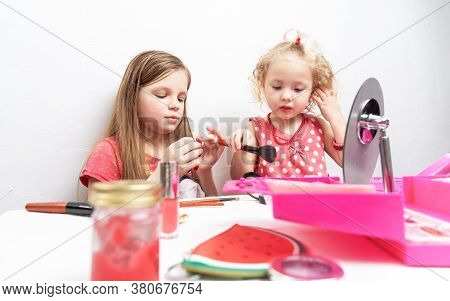 Baby Cosmetics: Two Little Girls Use Facial Cosmetics.