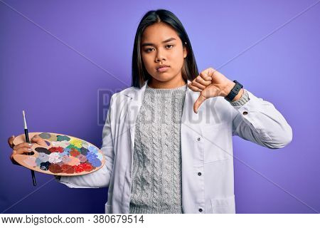 Young asian artist girl painting using paintbrush and palette with colors over purple background with angry face, negative sign showing dislike with thumbs down, rejection concept