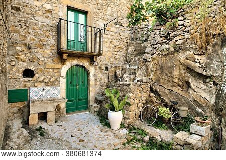 traditional architecture stone house of Sicily in old street of Mistretta village: door, balcony, wash-house, jar with prickly pear and bicycle