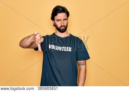 Young handsome hispanic volunteer man wearing volunteering t-shirt as social care looking unhappy and angry showing rejection and negative with thumbs down gesture. Bad expression.