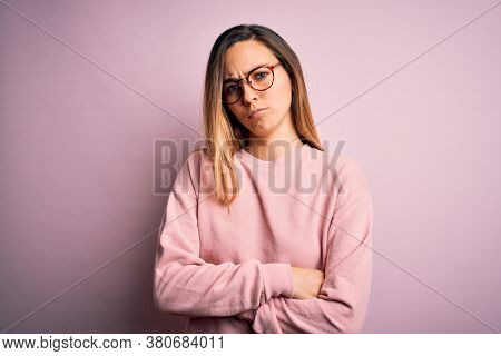 Beautiful blonde woman with blue eyes wearing sweater and glasses over pink background skeptic and nervous, disapproving expression on face with crossed arms. Negative person.
