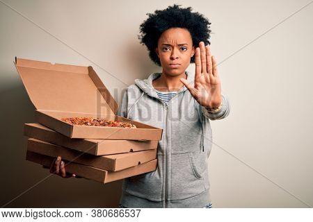 Young African American afro woman with curly hair holding delivery boxes with Italian pizza with open hand doing stop sign with serious and confident expression, defense gesture