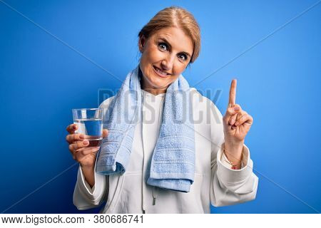 blonde sportswoman wearing towel drinking glass of water to refreshment surprised with an idea or question pointing finger with happy face, number one