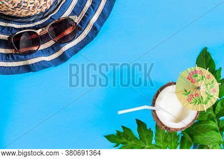 Striped Hat, Sun Glasses, Palm Leaves, Coconut Half With Milk Cocktail Are Laid Out On Blue Backgrou