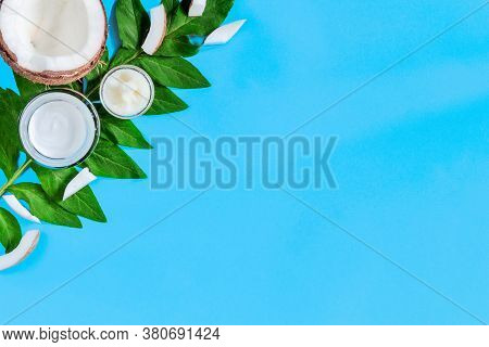 Cosmetics Jars With Coconut Creams, Oils Are Laid Out On Left Corner Of Blue Background. Summer Care