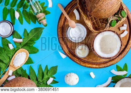 Cosmetics Bottles, Jars With Coconut Oils, Butters, Creams Are On Wooden Tray On Blue Background. Su