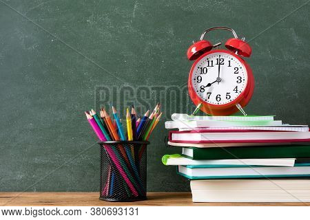 Education And Learning Background With Red Alarm Clock And Paper Notebooks With Colorful Pencils Aga