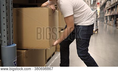 Warehouse Large Storage Or Logistic Or Cargo For Distribution. And Man's Hand Is Picking Up A Box.