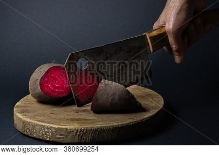 Beets, Cut In Half. A Hand Cuts Beets With A Rusty Kitchen Hatchet. Beets On Black Background