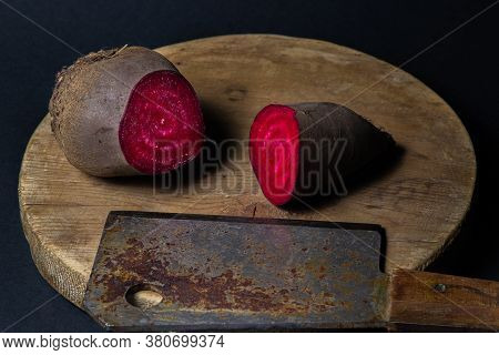 Beets, Cut In Half. Nearby Is A Rusty Kitchen Hatchet. Cooking Ingredient. Beets On Black Background