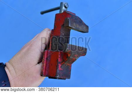 Small Iron Vise In Hand On A Blue Background