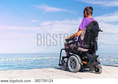 Man Sitting In A Wheelchair Looking At Sea. Head And Spine Injury. Dangers Of Jumping Into Water Fro