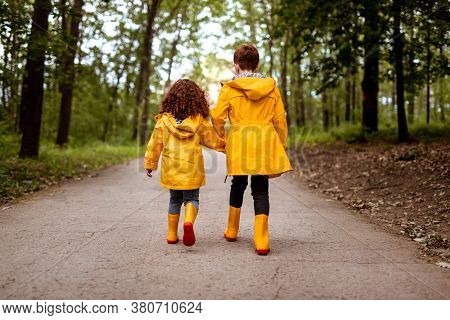 Back View Of Anonymous Ginger Brother And Sister In Raincoats Holding Hands And Walking On Asphalt P