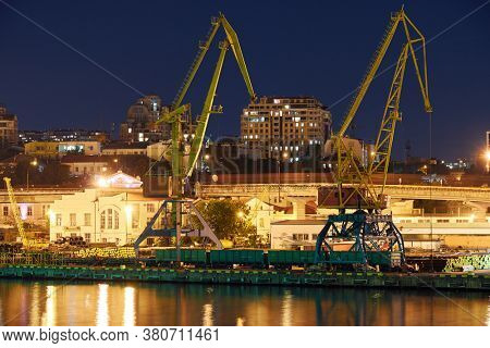view of the industrial port at night - ships waiting for loading and unloading, cargo transportation by sea