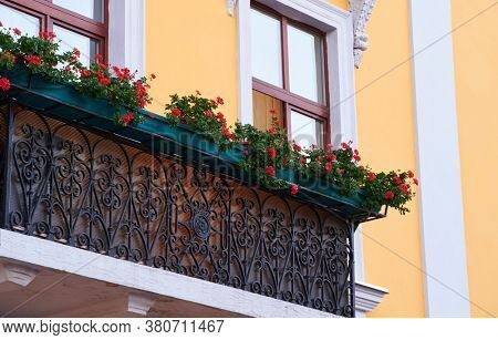 yellow wall and balcony decorated with flowers in the city