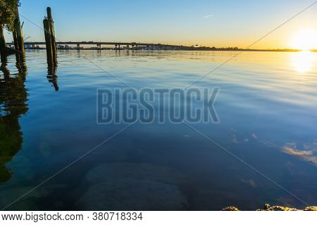 Tauranga Harbour Bridge Arches Across The Harbour In Distance Back-lit By Golden Sunrise Glow Betwee