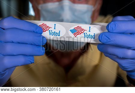 Election Volunteer With Face Mask And Medical Gloves Holding Roll Of I Voted Buttons With Usa Flag R
