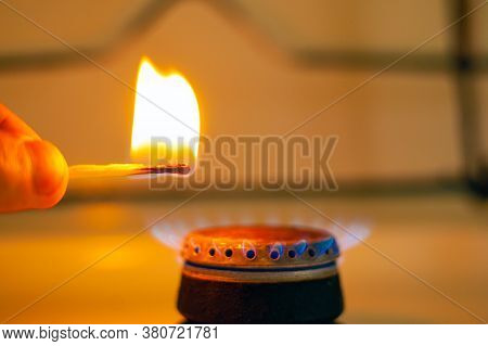 Man Lights A Gas Stove With A Match Close-up. Gas Stove With Burning Fire Propane Gas.