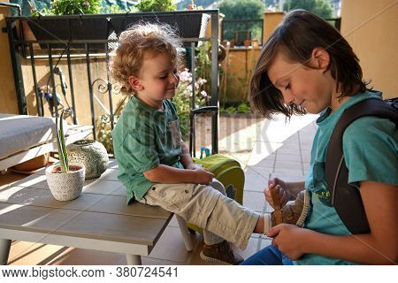 Boy Helping His Brother Tie Shoes Getting Ready For School, Child Buttoning Up Child's Laces, Young