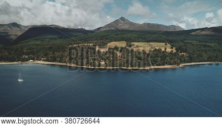 Scotland mountain Goatfell landscape aerial panoramic view at Brodick Harbour, Arran Island. Majestic Scottish nature scenery of forests, meadows and medieval castle.