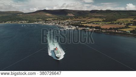 Scotland's ocean, passenger ferry aerial view in coastal water of Firth-of-Clyde Gulf. Ship crossing from Brodick terminal to Scottish mainland. Cityscape at green valleys.