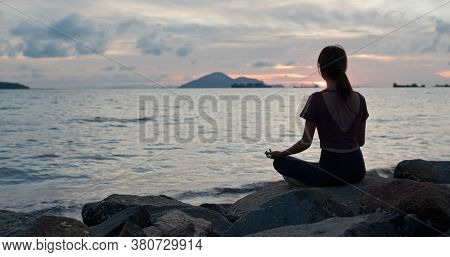 Woman do yoga at seaside