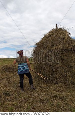 A Young Woman Throws Hay On A Wooden Support With A Hand Tool For Further Drying On The Field, The S