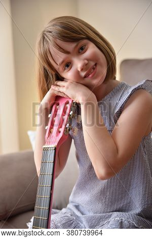 Girl Holding The Headstock Of A Guitar Looking And Smiling. Vertical Composition