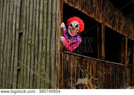 Halloween Holiday. Creepy Clown Costume. Spooky Clown In A Bright Overalls In An Wooden Hut.autumn H