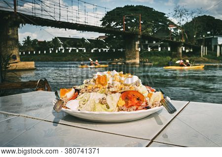 Food Of The National Lao Cuisine A White Plate On The Table In The Restaurant Located On The Bank Of